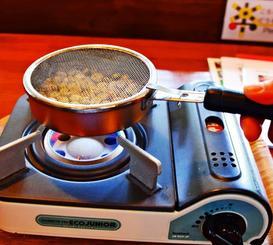 手摘みしたコーヒー豆をガスコンロで焙煎=本部町伊豆味、「cafe gyutto」
