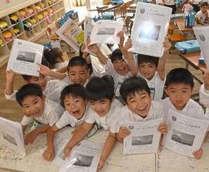 「よい子のあゆみ」を手に元気いっぱいの1年生=22日午前、浦添市・神森小学校