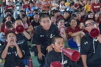 甲子園で熱戦を繰り広げる嘉手納ナインに声援をおくる地元少年野球部のメンバー=16日午前、嘉手納高校体育館