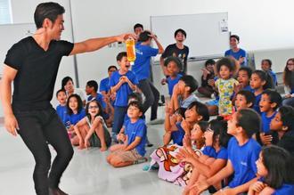 MASAさん(左端)のマジックに大興奮の子どもたち=8日、宜野湾市志真志のアメラジアンスクール・イン・オキナワ
