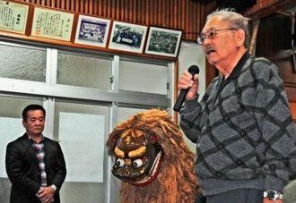 宮平区出身の父・赤嶺登助さんが作った獅子を前に、区民に話す三男トミオさん(右)=24日、同区公民館