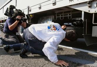 山陽自動車道で行われた、大型トラックのスペアタイヤの固定状況確認作業=17日午前、岡山市