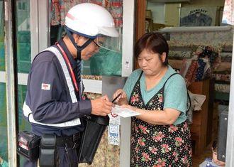 記載内容を確認しながら番号通知カードを受け取る住民=4日午前、与那原町