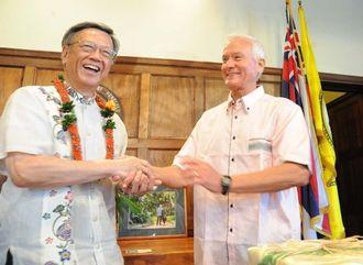 県から贈られたかりゆしウエアに着替え翁長雄志知事(左)と握手するコールドウェルホノルル市長=10日、ホノルル市庁