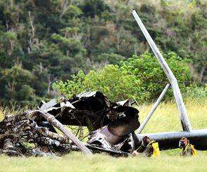 ガスマスク装着で機体残がい周辺に液体を散布する米軍関係者=12日午後4時過ぎ、東村高江(田嶋正雄撮影)