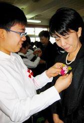 卒業式を前に、手作りしたバラのコサージュを親の胸に付ける6年生=24日、那覇市・安謝小学校