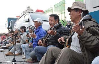「さんしんの日」に合わせ、米軍キャンプ・シュワブゲート前で三線を演奏する人たち=4日、名護市辺野古