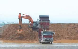 仮置き場所に辺野古埋め立て用土砂を降ろすダンプカ―=19日、名護市安和・琉球セメント桟橋付近