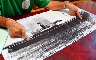対馬丸の写真資料を広げ、撃沈事件当時の記憶をたどる男性=那覇市内の自宅