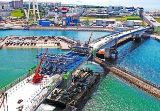 長さ約45メートル、重さ約390トンの橋げた部分(中央)が設置された国道58号浦添北道路の「牧港高架橋」=2017年8月、浦添市牧港(小型無人機から)