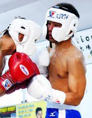 プロテストで左アッパーを打つ仲里健太(右)=12月9日、豊見城市真玉橋・平仲ボクシングスクールジム