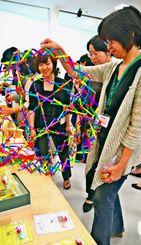 展示されたおもちゃを手に取る参加者=南風原町・沖縄小児保健センター