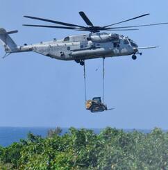 重機をつり下げて米陸軍トリイ通信施設に運搬する普天間飛行場所属のCH53E大型輸送ヘリ=27日午後1時38分、読谷村
