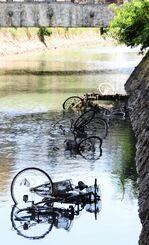 久茂地川に投げ捨てられた自転車=18日、那覇市の沖縄都市モノレール県庁前駅周辺