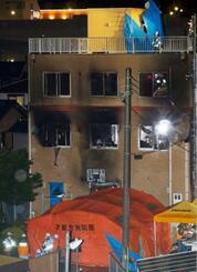 放火火災があったアニメ制作会社「京都アニメーション」のスタジオ。夜になっても捜索活動が続けられていた=18日午後7時23分、京都市伏見区
