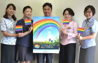 住宅ローンの夫婦連帯債務制度の対象を同性のパートナーにも広げると発表した琉球銀行の亀島健司調査役(中央)とローンセンターのセンター長ら=沖縄タイムス社