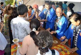 集まった人々にアグーの試食を配る関係者ら=31日、県庁前県民広場