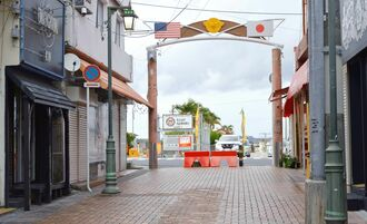 多くの店が閉まったままの繁華街とキャンプ・ハンセンメインゲートから出てくるYナンバー車両=15日、午後6時半ごろ、金武町