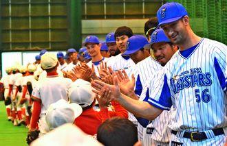 憧れのプロ野球選手とのハイタッチ。56番はウィーランド投手=10日、宜野湾市海浜公園室内練習場