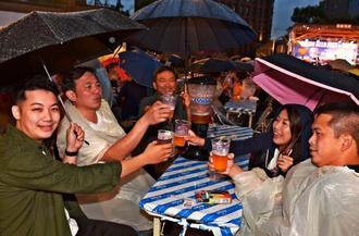 雨の中、オリオンビアフェスト・イン・台北を楽しむ台湾の人たち=13日午後、台北市内