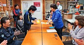 贈呈式で小麦粉を手渡す男子生徒(左奥から3人目)に大きな拍手が湧いた=3月9日、浦添市・港川中学校(同中提供)