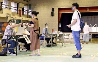 沖縄県議選の投票所で、新型コロナウイルス対策のため間隔を空けて並ぶ有権者=7日午前、那覇市