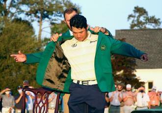 日本男子初のメジャー制覇を果たし、前年優勝のダスティン・ジョンソン(奥)にグリーンジャケットを着せてもらう松山英樹=オーガスタ・ナショナルGC(共同)