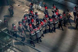 3日、銃や盾を装備し、デモ隊に向かって進む警官隊=ミャンマー中部マンダレー(AP=共同)