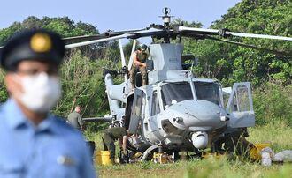 不時着したUH1ヘリのメンテナンス作業をする米兵=5日午前7時41分、うるま市・津堅島