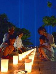 「平和の光の柱」が照射される平和の礎でともされたキャンドルを見る家族=22日午後8時、糸満市摩文仁
