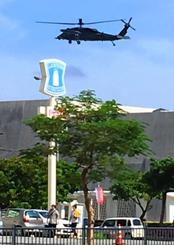 県立博物館・美術館の上空でホバリングする空自のヘリ=2日午前10時9分、那覇市おもろまち