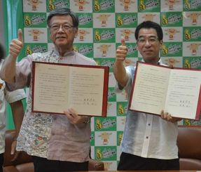 協定に調印し、県のグッジョブ!ポーズをとる翁長雄志知事(左)と沖縄労働局の待鳥浩二局長=20日、県庁
