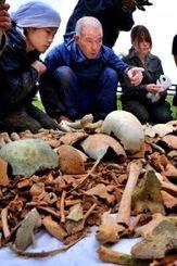 学生と収集した遺骨について話す国吉さん(中央)=2013年2月、糸満市大度(浜田哲二さん撮影)