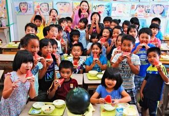 「みずみずしくて甘ーい」。読谷産の黒玉スイカをおいしそうに食べる2年2組の子どもたち=6月30日、読谷村・喜名小学校