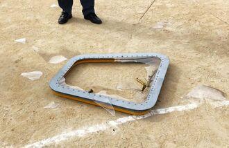 普天間第二小学校の運動場に落下した米軍のCH53Eヘリコプターの窓。周囲には割れた窓の破片が散らばっている(沖縄県宜野湾市提供)