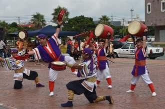 軽快なリズムの演舞で、道行く人の足を止める「創作エイサー舞天」のメンバー=20日、町美浜の観覧車前広場