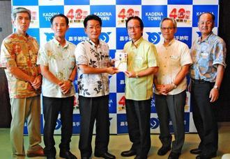 上原俊幸校長(左から3人目)に700万円の目録を手渡す當山宏町長ら=28日午後、嘉手納町役場