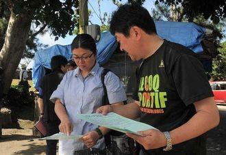 DNA鑑定集団申請の参加を遺族らに呼び掛ける「ガマフヤー」のメンバー(右)=23日午前9時25分ごろ、糸満市米須・魂魄の塔