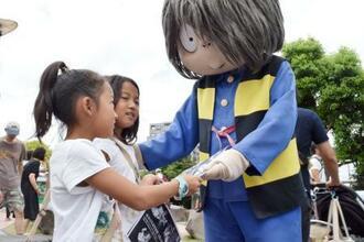 「第12回境港妖怪検定」のチラシを配る着ぐるみの鬼太郎=13日、鳥取県境港市