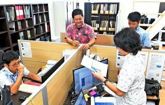 社内は外国のオフィスのような雰囲気。伊波貢さん(中央)は社員が働きやすいよう、ハード面の環境づくりにもこだわる=那覇市銘苅・ブルームーンパートナーズ