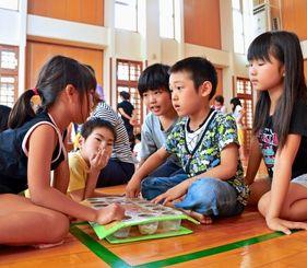 「まんから」のボードを挟んで対戦する子どもたち=7日、浦城っ子児童センター