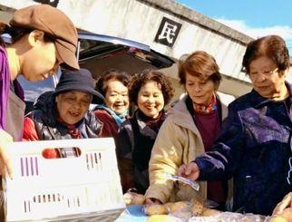 高齢者が楽に通えるよう公民館前に開店した「えぐち商店」。パンを買い求めるお年寄りらが集まり、自然と笑顔が広がった=北谷町栄口区公民館
