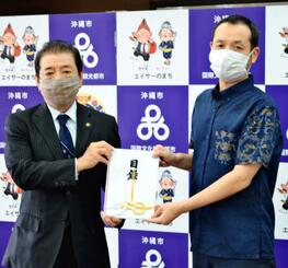 桑江朝千夫市長(左)に寄付金を手渡す木村達郎社長=13日、沖縄市役所