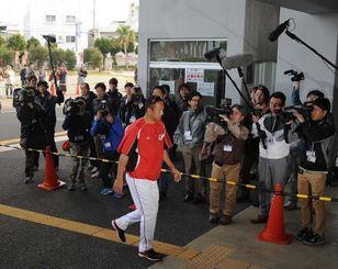 多くの報道陣が集まる中、球場に入る広島東洋カープの黒田博樹投手=18日午前8時50分ごろ、沖縄市・コザしんきんスタジアム