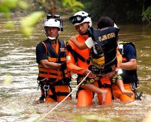 消防隊員に抱えられ救助される女の子=5日午後6時4分、名護市源河川