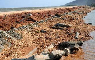 台風24号の暴風と高潮で、舗装が約200メートルにわたってはがれ、のり面も崩れた久米島町道=1日、同町北原(比嘉正明通信員撮影)