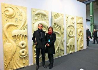 作品「神話の世界」の前に立つ幸地学さん(左)と妻のみどりさん