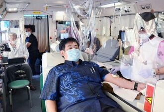 大興建設が受け入れている県赤十字血液センターの移動献血の協力者。献血バス内では感染予防のため、献血車と看護師の間にビニールカーテンを設けていた=12日、嘉手納町海浜公園駐車場