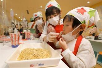 自分だけのベビースターラーメンを試食する子ども=29日、大阪市