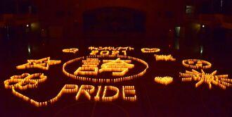 子どもたちが描いた紙コップを使い、光文字を浮かべた=16日、沖縄市・美東中体育館